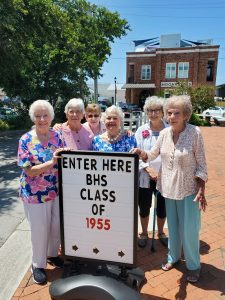 Six women surrounding a class of 1955 sign